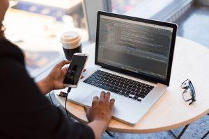 Männerhand mit Handy und Laptop im Hintergrund