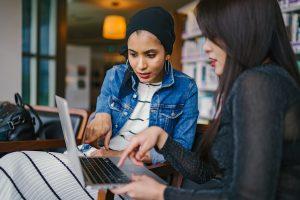 Zwei junge Frauen beim Ausfülllen einer Meinungsumfrage am Computer