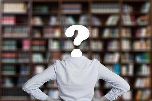 Student mit symbolischen Fragezeichen statt Kopf stehrt vor einer Bücherwand