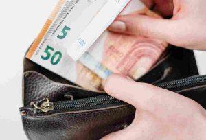 Frau steckt drei Geldscheine in Geldbörse