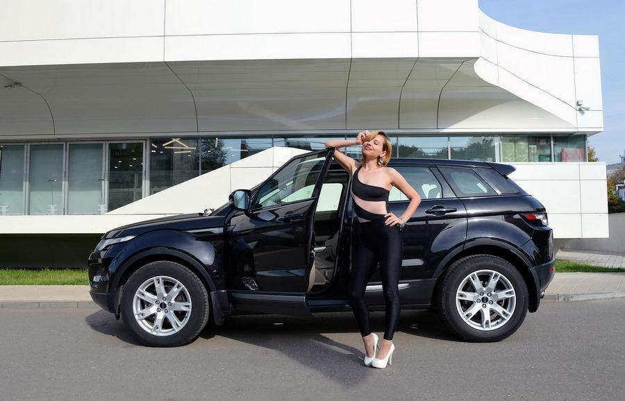 Frau vor schwarzem Auto