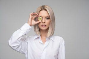 Junge Frau hält sich Bitcoin vor ein Auge