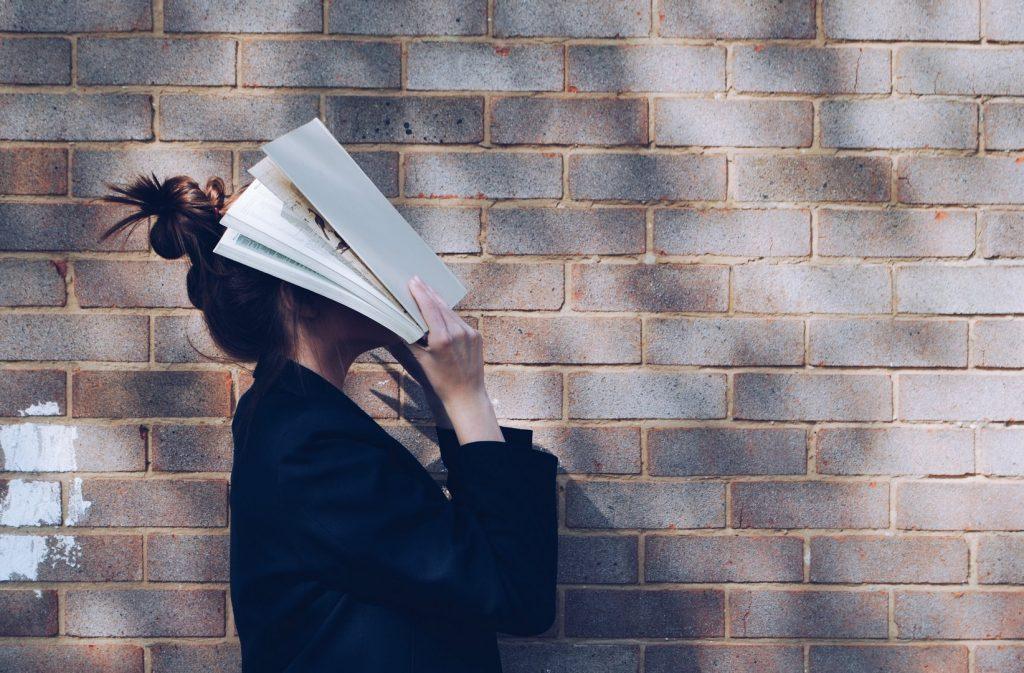 Studentin vor Mauer