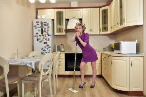 Hausfrau steht in Küche mit Besen